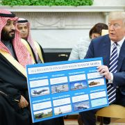 U.S. President Donald Trump (R) holds a defense sales chart with Saudi Arabian Crown Prince Mohammed bin Salman in the Oval Office on March 20.