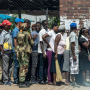 A Zimbabwean soldier watches shoppers lining up in Bulawayo on Jan. 17, 2019.