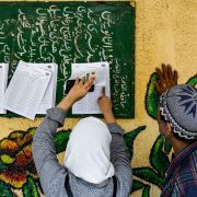 Egyptians view a voter manifest to find the correct polling station