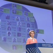 The European Commission's president-elect, Ursula von der Leyen, talks to the media during the unveiling of her new team for the 2019-2024 term. A graphic showing the specific commissioners is displayed on a large screen behind her.