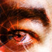 Abstract montage of a man's eye with a radar grid overlaying the pupil.