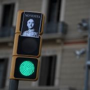 """A picture taken on Sept. 23 shows a sticker depicting Spanish dictator Francisco Franco with a message reading """"Don't vote"""" on a traffic light in downtown Barcelona."""