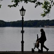 A woman uses an aid to walk along Berlin's Lake Tegel in June 2017.