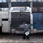 A man walks past closed shops in the center of the Greek city of Thessaloniki on June 21, 2018.