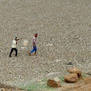 Workers carry water collected from Puzhal lake on June 20, 2019. Puzhal is one of four main reservoirs that supply the southern Indian city of Chennai with water; all are running dry.