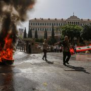 A protester passes a burning tire during a demonstration over feared pension cuts May 20, 2019, near the government's headquarters in Beirut.