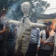 Indian traders shout slogans as they burn an effigy representing a tax worker during a protest against an upcoming new Goods and Services Tax (GST) rates in New Delhi.