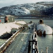 The ill-fated Kursk submarine (L) sits in port in the winter of 2000.