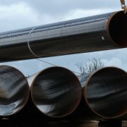 A section of pipe hangs from a crane at a construction site of the Eugal gas pipeline in Germany, which will transport natural gas arriving from Russia through the Nord Stream 2 pipeline.
