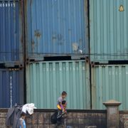 People pass a wall of shipping containers in Manila.