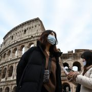 Two women wearing blue, protective respiratory masks take a tour outside the Colosseum in Rome, Italy, on Jan. 31, 2020, after two cases of the new coronavirus were confirmed in the city.