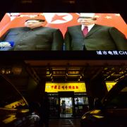 News footage of North Korean leader Kim Jong Un, left, and Chinese President Xi Jinping is shown above a Beijing restaurant on March 28, 2018.