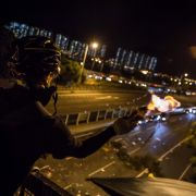 This photo shows a protester in Hong Kong throwing a Molotov cocktail to stop vehicles from passing through a barricade beneath a bridge at the Chinese University of Hong Kong on Nov. 15, 2019.