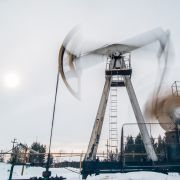 A photo of a pump jack extracting crude oil from a snow-covered well located near Surgut, Russia.