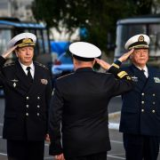 Military officials salute each other in a ceremony before Russia and China warships set out for a naval cooperation exercise.