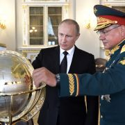 Russian President Vladimir Putin (C) and Defense Minister Sergei Shoigu visit the headquarters of the Russian navy in 2017.