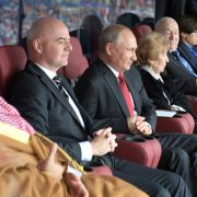 Russian President Vladimir Putin (C) watches the opening game of the 2018 World Cup next to FIFA President Gianni Infantino (L), who has praised him for the turnout at the tournament.