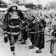 Different generations of samurai mingle at a pageant in Japan, circa 1930.