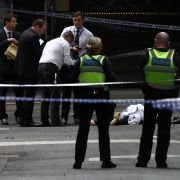 Police examine a body on a street in Melbourne on Nov. 9, 2018. A man was shot by police after setting his car on fire and stabbing three people, killing one. The man was arrested at the scene and taken to hospital in critical condition.
