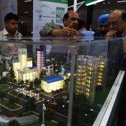 "Attendees at an expo in New Delhi, India, take in a model of a ""smart city,"" an urban area wired with connected information and communication technology systems."