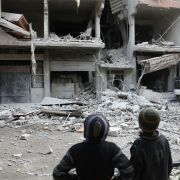 Children survey the damage to a building just outside Damascus that sustained a missile attack from forces loyal to the Syrian government Jan. 18.