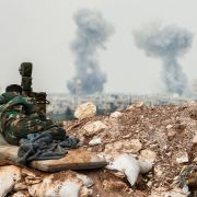 A Syrian government forces soldier observes artillery fire on April 1, 2017, near Qumhanah in the central province of Hama.