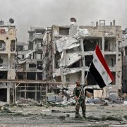 A member of the Syrian pro-government forces plants the national flag in front of damaged buildings in the Yarmouk Palestinian refugee camp on the southern outskirts of the capital Damascus during May 2018.