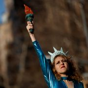 A young woman takes to the stage dressed as the Statue of Liberty for a demonstration on International Women's Day in New York City.