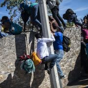 Central American migrants, mostly from Honduras, climb over a barrier as they try to reach the U.S.-Mexico border on Nov. 25, 2018, near the El Chaparral border crossing in Tijuana, Baja California State, Mexico.