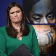 White House Press Secretary Sarah Huckabee Sanders stands in front of photos from the MS-13 gang during a White House daily briefing July 27, 2017.