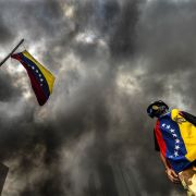 An anti-government demonstrator stands next to the Venezuelan national flag during an opposition protest blocking the Francisco Fajardo highway in Caracas in May.