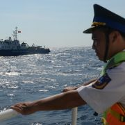 A Vietnamese coast guard officer looks toward a Vietnamese coast guard ship sailing in an area near a Chinese oil-drilling rig in disputed waters of the South China Sea, in May 2014.