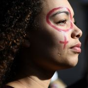 A woman with the female gender pictogram made up on her face attends a demonstration as part of the 40th International Women's Day on March 8, 2017 in Marseille.