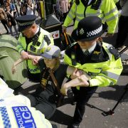 Police officers carry away an activist during an Extinction Rebellion protest in central London on April 19, 2019.