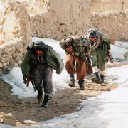 A group of Afghan mujahideen progress behind a wall in the village of Ghazni in southern Afghanistan as they fight Soviet-backed government forces in March 1989.