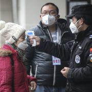Authorities in Wuhan, China, check the temperature of a passenger at a wharf on the Yangtze River on Jan. 22, 2020.