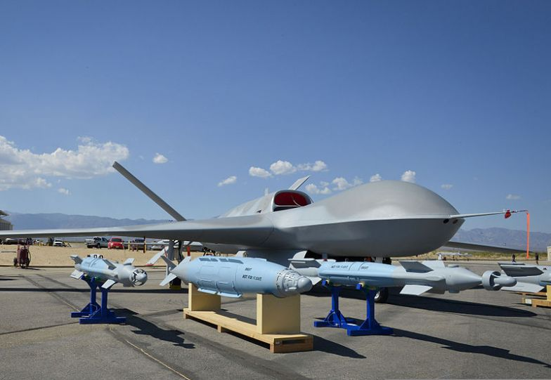 An Avenger unmanned aircraft system and inert ordnance sit on display on a tarmac at Palmdale, Calif., Aug. 8, 2012.