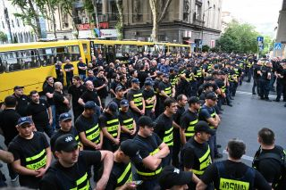 Police forces line up in the road, preparing to disband the demonstration.