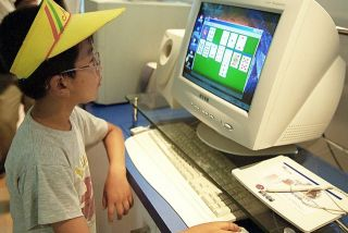 A child plays a game on a personal computer at a Beijing fair in July 2000.
