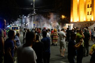 Protesters cover their faces as tear gas is fired into the crowd.