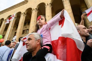 A young girl wearing an eye patch and holding a Georgian flag joins the protest.