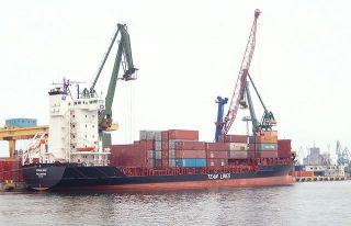 A container ship unloads its cargo. It enables manufacturers to ship their goods abroad without having to contend with lacking transportation infrastructure.