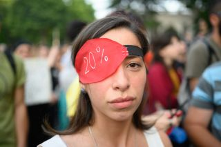 A woman wears an eye patch in protest of the dispersal of the protest.