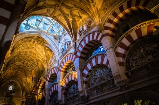 Rib vaults give way to the iconic striped arches of the Cordoba mosque or cathedral.