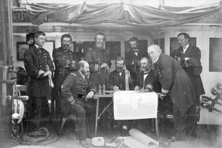 U.S. Navy officers aboard the Asiatic Squadron flagship off the coast of Korea in June 1871. Asiatic Squadron commander Rear Adm. John Rodgers (R) leans on the table. Korea eventually opened its ports in a treaty, paving the way for a treaty with the United States in 1882.
