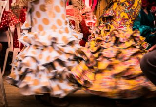 Women wear bright, flouncy skirts at the Feria in Seville.