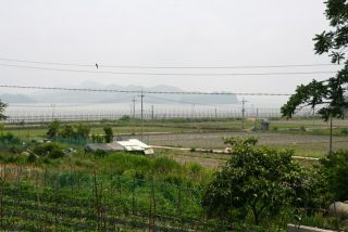 A South Korean farm along the wire fence on the island of Ganghwado. South Korea controls the island. North Korea is on the far shore.