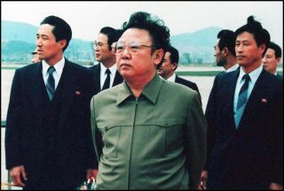 The late North Korean leader Kim Jong Un (center) waits on the tarmac at Pyongyang's airport in 1992.