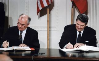This image shows Soviet leader Mikhail Gorbachev and U.S. President Ronald Reagan signing the Intermediate-Range Nuclear Forces Treaty in 1987.