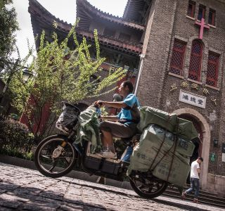 A delivery man rides his bike in front of a Christian church on Duolun street in Shanghai during 2016.